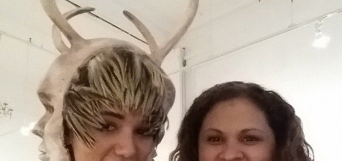Melanie Gonzalez wearing the head piece for Yelaine Rodriguez dress at Innuendos art exhibition, with co-curator Yolanda Rodriguez